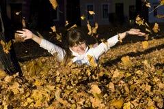 La fille sur des lames d'automne Photo stock