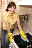 La fille sur la cuisine essuie un cuiseur de gaz Photographie stock