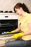 La fille sur la cuisine essuie un four Images libres de droits