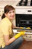 La fille sur la cuisine essuie un four Photo stock