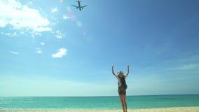 La fille sur la plage et l'avion décollent banque de vidéos