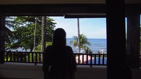 La fille sur le balcon de l'hôtel regarde la mer banque de vidéos