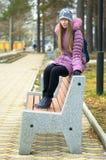 La fille sur le banc. Image libre de droits