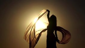 La fille sur le bord de la mer danse avec élégance son corps contre le coucher du soleil Silhouette Mouvement lent clips vidéos