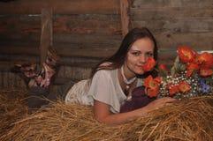 La fille sur le foin avec des fleurs Images stock