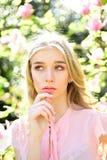 La fille sur le visage rêveur, magnolia proche blonde tendre fleurit, fond de nature Concept de fleur de ressort Madame marche en Images libres de droits