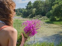 La fille sur la nature avec un sac à dos et rassemble des herbes image libre de droits