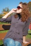 La fille sur un banc parle par le téléphone Images stock