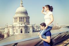La fille sur une épaule du ` s d'ami regarde vers la ville Photo stock
