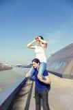 La fille sur une épaule du ` s d'ami regarde vers la ville Image libre de droits
