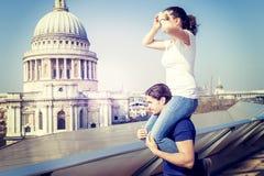 La fille sur une épaule du ` s d'ami regarde vers la ville Photographie stock