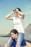 La fille sur une épaule du ` s d'ami regarde vers la ville Images stock