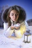 La fille sur une clairière d'hiver souffle sur des flocons de neige Images libres de droits