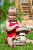 La fille sur une pelouse s'assied avec un champignon de couche de jouet Photo libre de droits