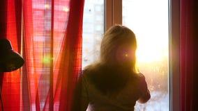 La fille tôt le matin se tenant à la fenêtre et se peigne les cheveux Les rayons du ` s du soleil traversent le verre illuminent banque de vidéos