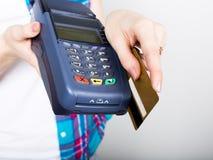 La fille tenant un terminal de position, client paye par la carte de crédit terminal de carte de crédit d'argent électronique et Image stock