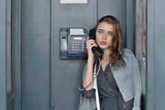 La fille tenant une cabine téléphonique a fixé à la main dans sa main photos stock