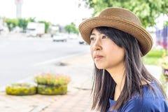 La fille thaïlandaise de l'Asie s'asseyent sur la voiture wating d'arrêt d'autobus Image libre de droits