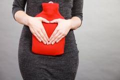 La fille tient la bouteille d'eau chaude sur le ventre faisant la forme de coeur à la main photographie stock