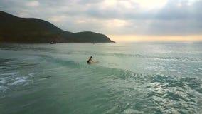 La fille tient des essais de planche de surf pour se reposer et monter sur des vagues banque de vidéos