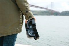 La fille tient des verres de réalité virtuelle Jetez un pont sur le 25 avril à Lisbonne au Portugal à l'arrière-plan Image stock