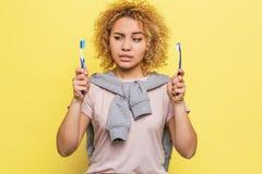 La fille tient deux brosses de dents dans des ses mains et regarde l'une d'entre elles Sa vue est méfiante Elle le ` t de doesn s Photo stock