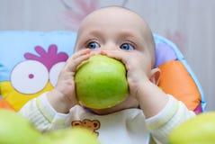 La fille tient la pomme verte de deux mains et le mord Photos stock