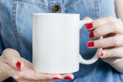 La fille tient la tasse blanche dans des mains photos stock