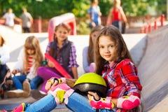 La fille tient le casque portant se reposer intégré de patins Photos libres de droits
