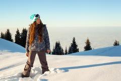 La fille tient le dessus de montagne au coucher du soleil Image libre de droits