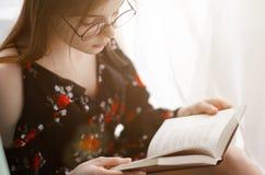 La fille tient le livre intéressant Image stock