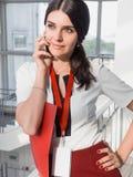 La fille tient le téléphone dans des ses mains La belle femme d'affaires de sourire appelle par le téléphone Portrait de femme d' Photographie stock