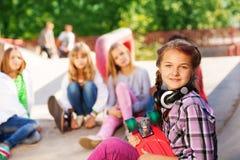 La fille tient les écouteurs de port de planche à roulettes Photos stock