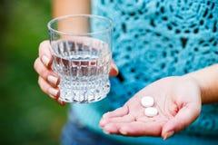 La fille tient les pilules médicinales Photo stock