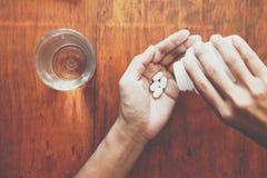 La fille tient la médecine dans sa main avec un verre de l'eau sur une table en bois Photographie stock libre de droits