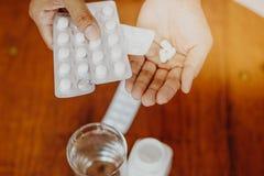 La fille tient la médecine dans sa main avec un verre de l'eau sur une table en bois, prennent une médecine Photo stock