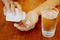 La fille tient la médecine dans sa main avec un verre de l'eau sur une table en bois, prennent une médecine Photographie stock
