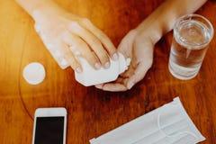 La fille tient la médecine dans sa main avec un verre de masque protecteur de l'eau et le téléphone intelligent sur une table en  Photographie stock libre de droits