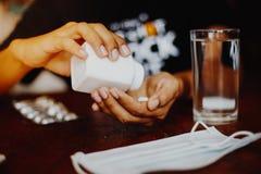 La fille tient la médecine dans sa main avec un verre de masque protecteur de l'eau sur une table en bois Photographie stock