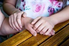 La fille tient la main du ` s de mère dans des ses mains La fille image stock
