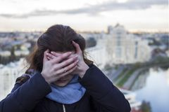 La fille tient sa tête avec les deux mains Mal de tête Effrayé des tailles Photo libre de droits
