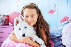 La fille tient un chien dans la chambre Le concept de l'amitié et de la vie Photographie stock libre de droits