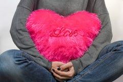 La fille tient un coeur cramoisi d'oreiller, amour Photo stock