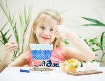 La fille tient un doigt tout en préparant une fondue de chocolat Images stock