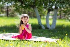 La fille tient un verre avec du jus dans des ses mains photo libre de droits