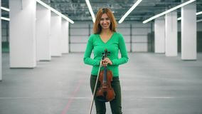 La fille tient un violon dans les mains et les sourires à une caméra banque de vidéos