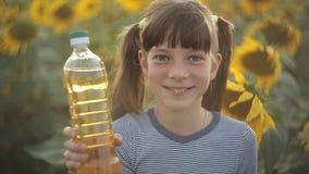 La fille tient une bouteille d'huile végétale et de supports dans le domaine avec des tournesols Nourriture d'agriculture, orga clips vidéos