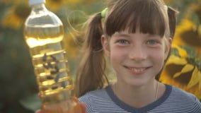 La fille tient une bouteille d'huile végétale et de supports dans le domaine avec des tournesols Nourriture d'agriculture, orga banque de vidéos