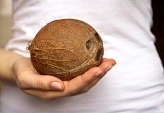 La fille tient une noix de coco Photographie stock libre de droits