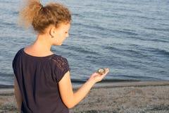 La fille tient une petite boussole indiquant la direction sur le fond de la mer images libres de droits